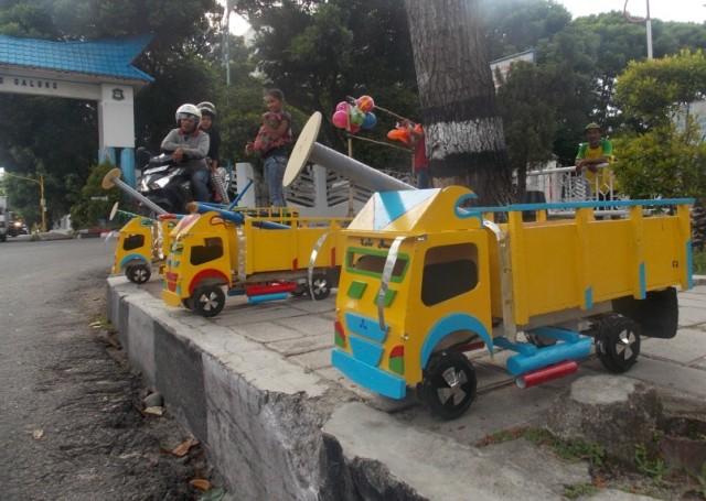 Miniatur truk kayu berjejer di trotoar Lapangan Adam Malik