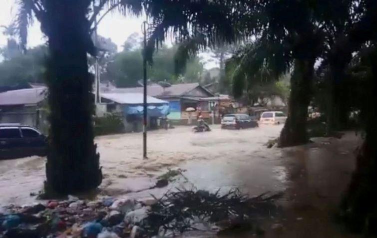 Air Banjir dari kebun Marjandi tampak meluap ke jalan dan pemukiman.
