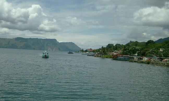 Kapal ferry penyeberangan di perairan pantai Tomok, Danau Toba. (isiantar/nda).