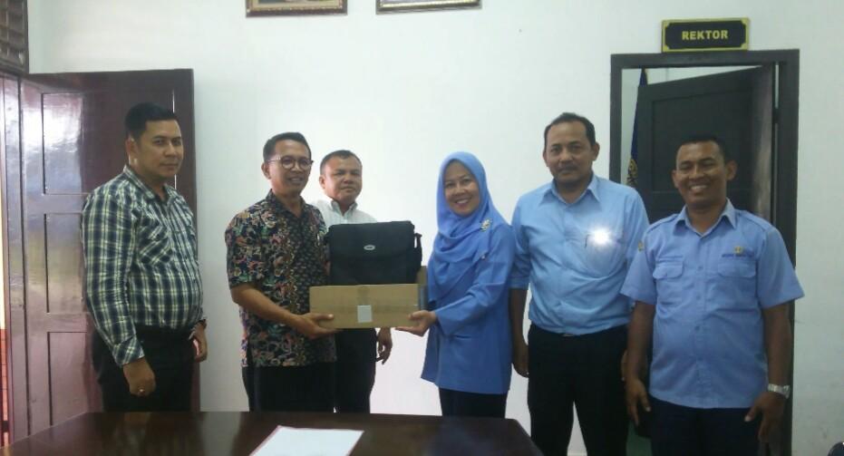 Rektor UHKBPNP, Prof Dr. Sanggam Siahaan M.Hum, saat menerima bantuan dari PDAM Tirta Uli yang diserahkan oleh Kabag Humas Rosliana Sitanggang, Selasa (1/10/2019). (isiantar/nda).