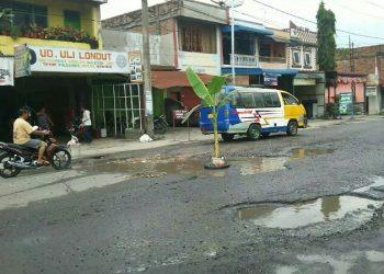 Salah satu pohon pisang yang ditanam warga di badan Jalan Pdt Justin Sihombing, Senin (25/11). (isiantar/nda).