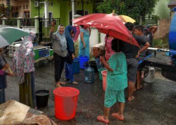 Warga Karangsari antri mengambil air dari mobil tangki gratis PDAM Tirtauli, Jumat sore (20/3/2020).