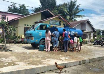 Masyarakat Jl Manunggal Karya tampak antri mengambil air dari mobil tangki gratis PDAM Tirtauli, Kamis (28/5) pagi.