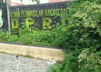 Penampakan taman dan kolam hias DPRD Siantar di Jalan Adam Malik, yang tak hanya disesaki belukar dan sampah namun juga dipenuhi botol-botol minuman, Kamis (9/7). (isiantar/nda).
