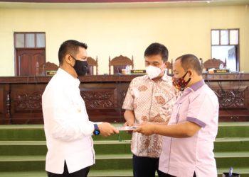 Ketua DPRD Kota Siantar, Timbul Lingga, menyerahkan berita acara Perda Perumda Air Minum Tirtauli kepada Walikota Siantar, Hefriansyah, Selasa (27/10).