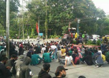 Massa pengunjukrasa memblokir dan menduduki badan Jalan Sudirman, Kamis (15/10). (isiantar/nda).