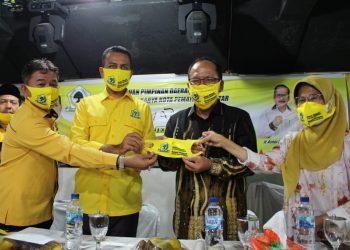 Drs H Musa Rajekshah M.hum dan Mangatas Silalahi menyerahkan masker Golkar kepada Ir Asner Silalahi Mt bersama dr Susanti Dewayani SpA.