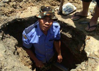 Seorang petugas PDAM Tirtauli tengah melakukan perbaikan pipa.