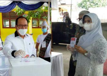 Asner Silalahi (kiri), Susanti Dewayani (kanan), saat menggunakan hak suara mereka di TPS, Rabu (9/12/2020).