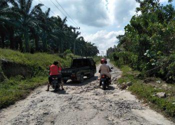 Tiga unit kendaraan tampak sedang berjuang melintasi salah satu ruas jalan yang rusak di Kabupaten Simalungun, Sabtu (27/2) siang. (isiantar/Us).