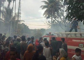 Kerumanan warga tengah menyaksikan upaya pemadaman api kebakaran oleh Damkar Siantar, Jumat (5/3) sore. (isiantar/jw-NM).