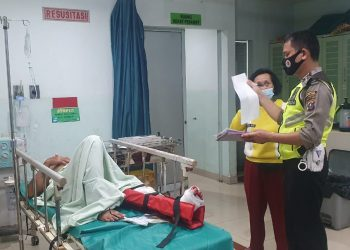 Salah seorang pengendara tampak terbaring di rumah sakit usai terkapar di atas aspal akibat kecelakaan di Asahan dekat Kompleks Megaland, Selasa (20/4) pagi.