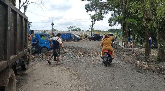 Dua perempuan berseragam ASN tengah melintas dari badan jalan yang berlubang dan dipenuhi rembesan sampah TPA Tanjung Pinggir, Senin (17/5/2021). (isiantar/nda).